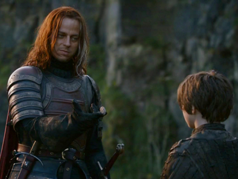 Jaqen H'ghar, a Faceless Man of Braavos, handing an iron coin to Arya Stark in Game of Thrones, season 2, photo: HBO