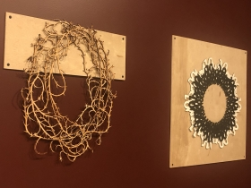 "Necklaces by (left) Nancy Slagle (""Brambles"") and (right) Nancy Slagle (""Binary 001"") mounted to the wall in the exhibition ""Not"